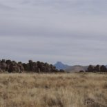Distant mountains, grassy plains, pile 'o rocks in the middle.