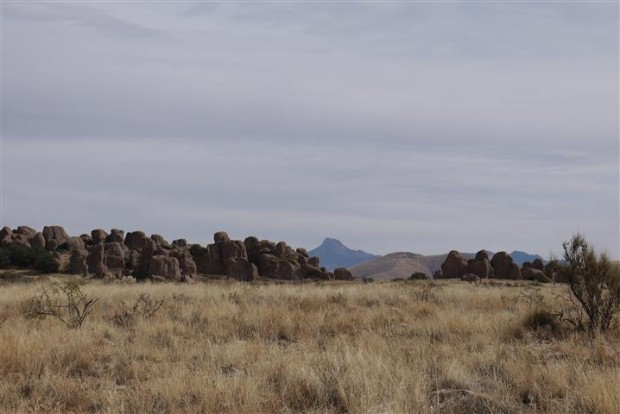 Distant mountains, grassy plains, pile 'o building-sized rocks in the middle.