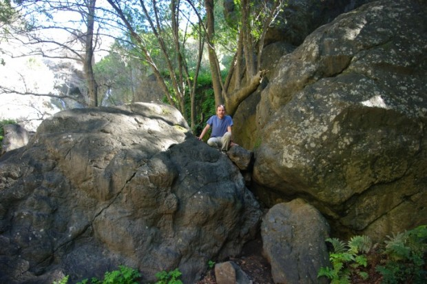 Paul climbing around on the slippery boulders.