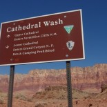 The sign along the road marking Cathedral Wash. Vermillion Cliffs in the background.