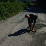 Paul trying to show the depth of a major pothole.